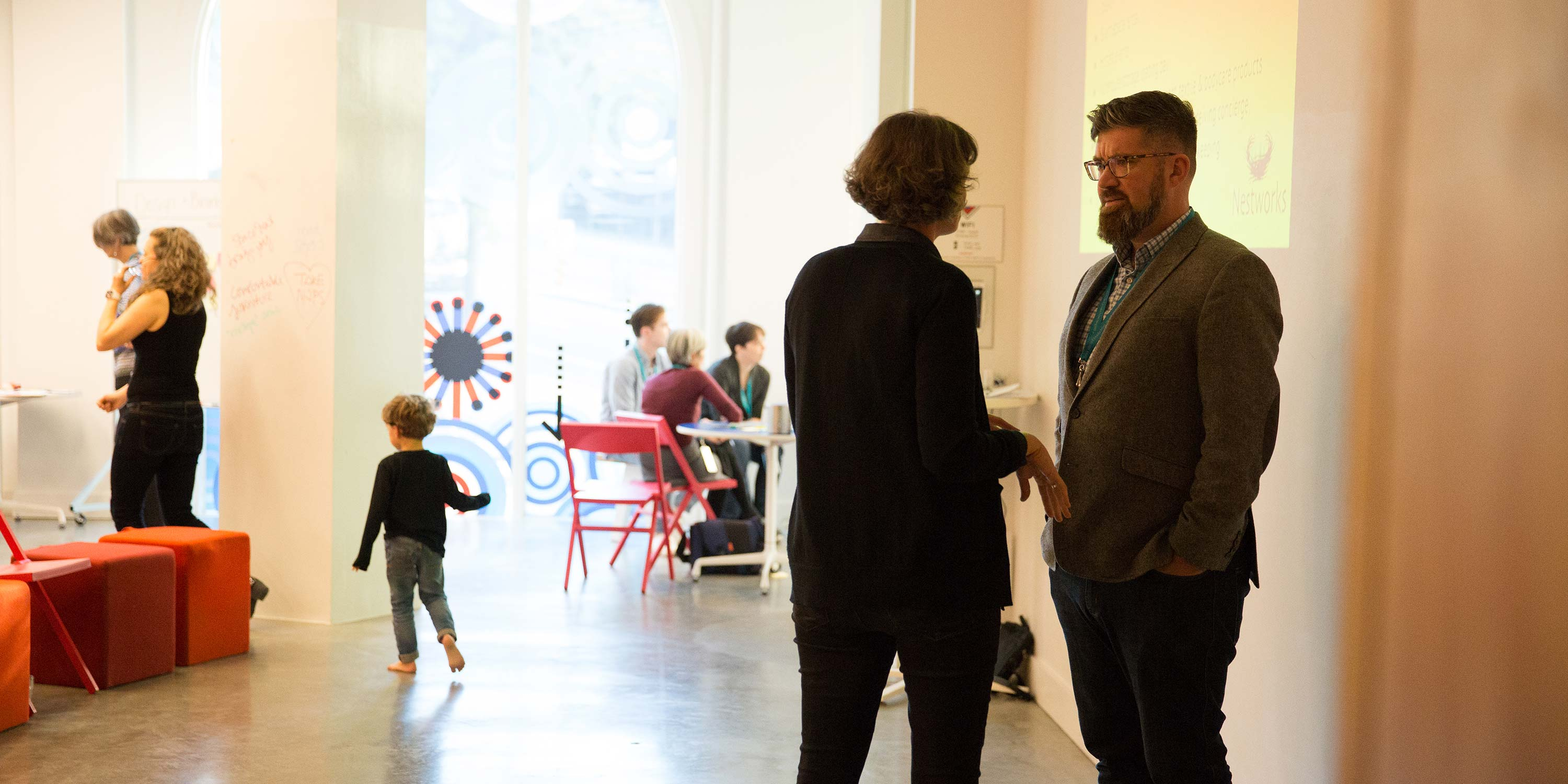 well-lit hallway, male and female talking in foreground, toddler running in middle, group of people in background